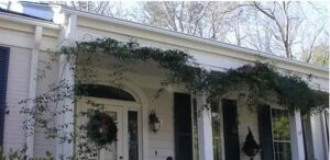 Large white house with vines